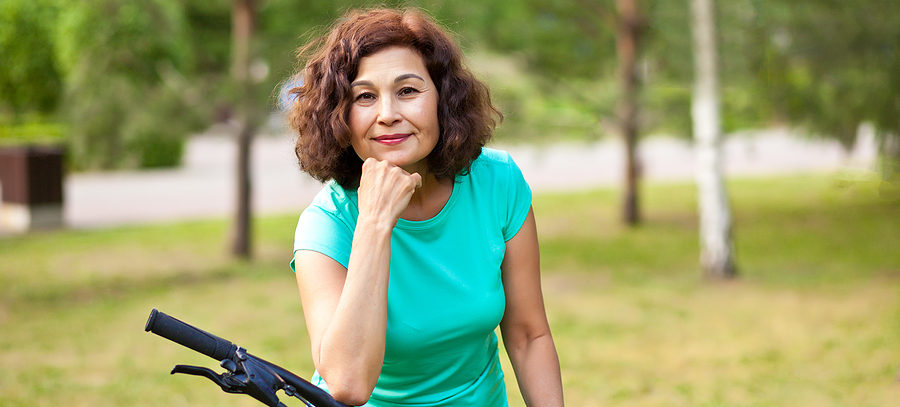 Middle age senior woman on bike cycle ride in countryside park outdoor